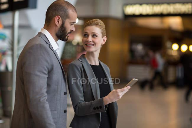 Pareja feliz usando teléfono móvil en el aeropuerto - foto de stock
