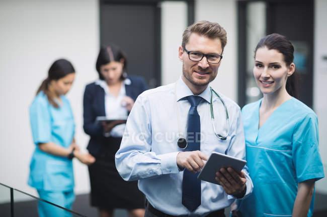 Retrato de sonriente doctor y enfermera con tableta digital en pasillo de hospital - foto de stock