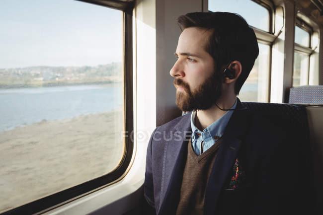 Задумчивый бизнесмен смотрит в окно поезда — стоковое фото