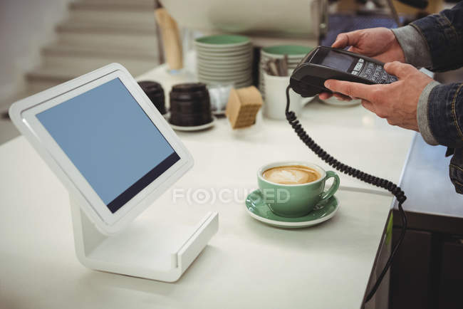Hands of man using edc machine at billing counter in coffee shop — Stock Photo
