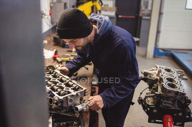 Mecánico de comprobación de un coche de piezas en el garaje de reparación - foto de stock