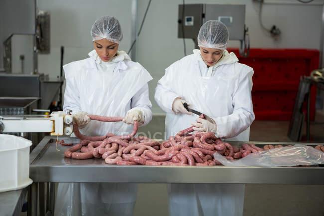 Самки Різники різання ковбаски на заводі м'яса — стокове фото
