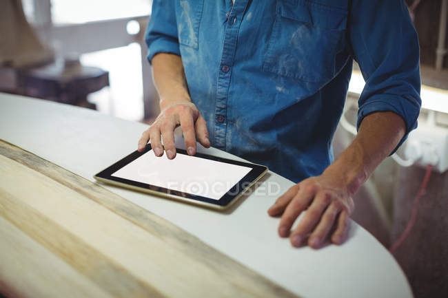Sezione media dell'uomo utilizzando tablet digitale in laboratorio tavola da surf — Foto stock