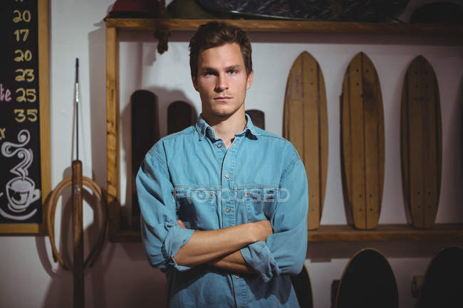 Confident man standing with arms crossed in surfboard shop — Stock Photo
