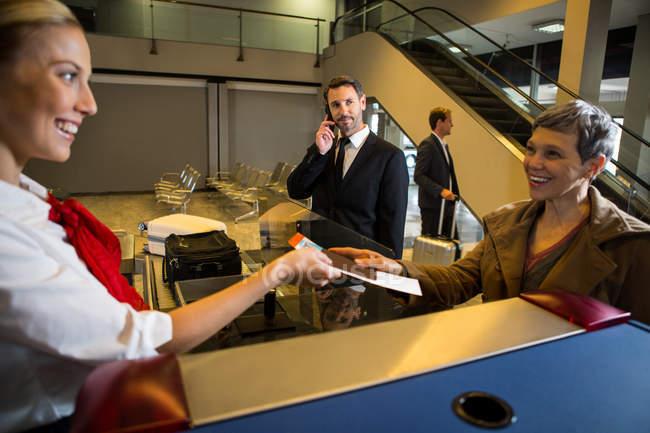 Funcionários do sexo femininos dando embarque aprovado para o passageiro no aeroporto terminais — Fotografia de Stock