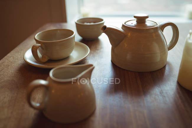 Théière et café tasse sur la table en bois dans le café — Photo de stock
