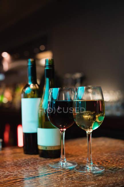 Очки, красное и белое вино и бутылки на барной стойкой в бар — стоковое фото