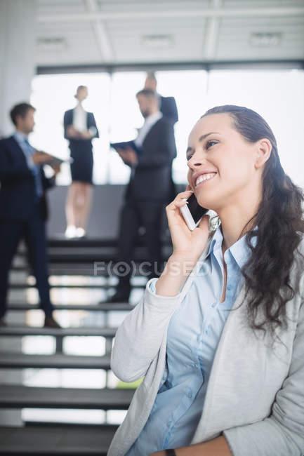 Деловая женщина разговаривает по мобильному телефону в офисе — стоковое фото