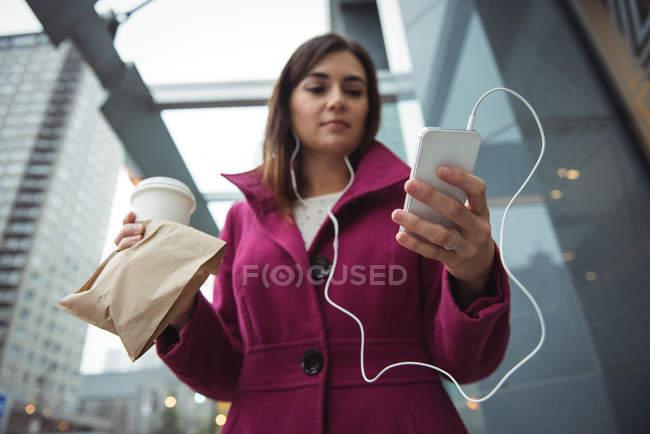 Empresaria sosteniendo taza de café desechable y paquete mientras escucha música cerca del edificio de oficinas - foto de stock
