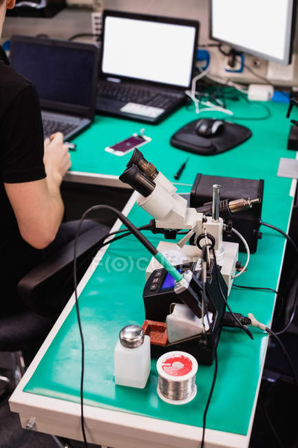 Industrial microscope and soldering iron with solder in a repair centre — Stock Photo