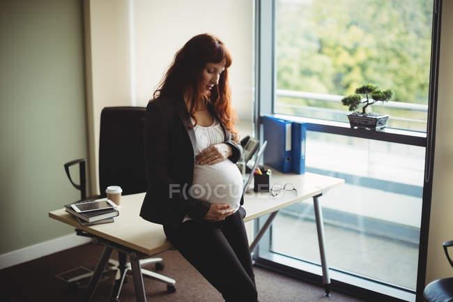 Беременная деловая женщина, трогающая живот в офисе — стоковое фото