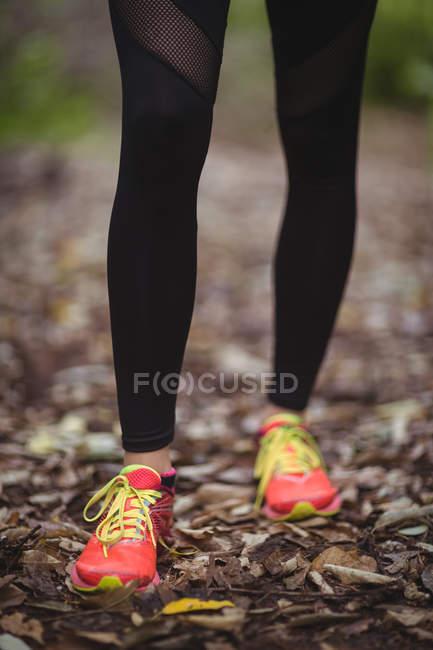 Женщина в спортивной обуви, стоящая в лесу — стоковое фото