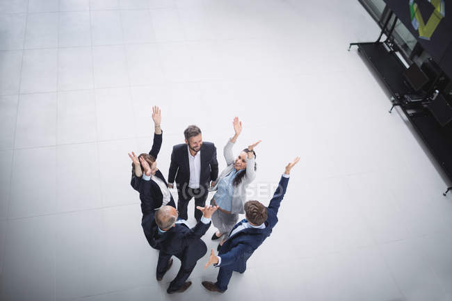 Business people standing with hands raised — Stock Photo