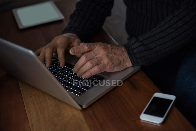 Mid-section of man sitting at table and using laptop at home — Stock Photo