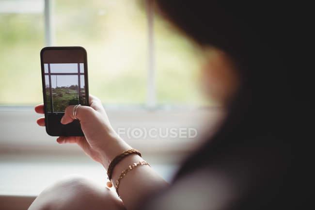 Rückansicht der Frau, die ein Foto auf dem Handy aus Fenster — Stockfoto