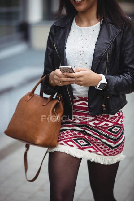 Woman using mobile phone while walking in office premises — Stock Photo