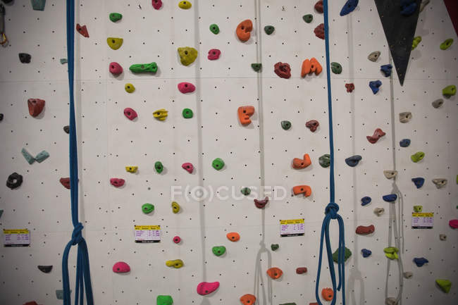 Mur d'escalade artificiel au gymnase pour la pratique — Photo de stock