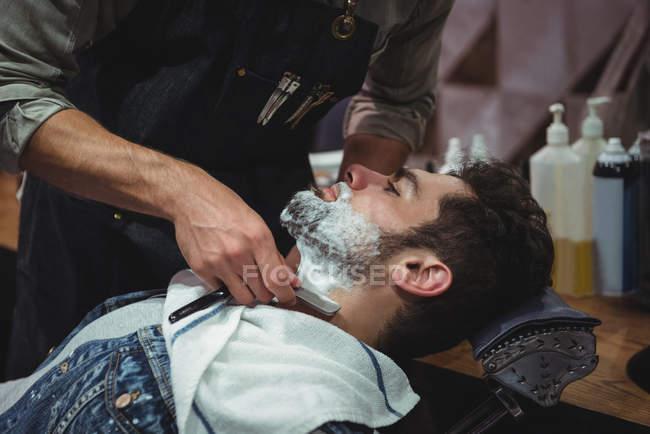 Клиент, как борода бритые с бритвой в парикмахерской — стоковое фото