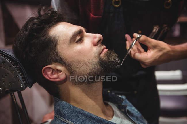 Uomo ottenere barba tagliata con le forbici in negozio di barbiere — Foto stock