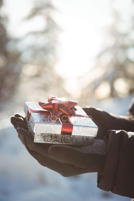 Gros plan des mains masculines tenant un cadeau pendant l'hiver — Photo de stock