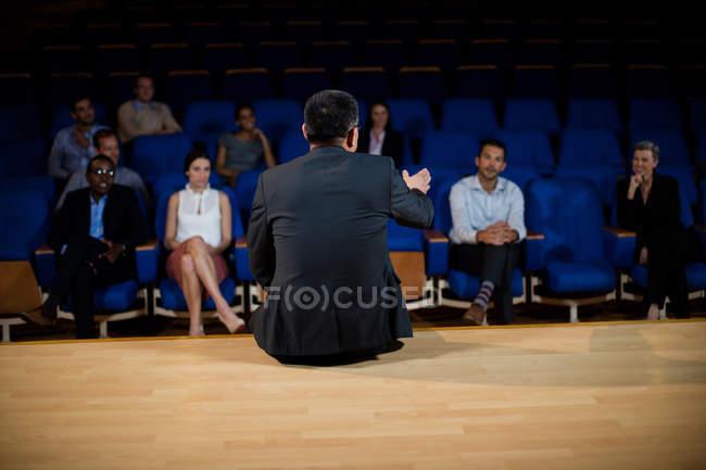Vue arrière d'un homme d'affaires parlant à ses collègues du centre de conférence — Photo de stock