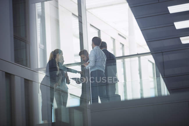 Group of business people interacting in corridor of an office building — Stock Photo
