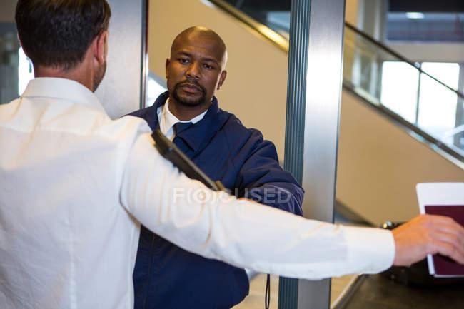 Guardia de seguridad registrando pasajeros en la terminal del aeropuerto - foto de stock