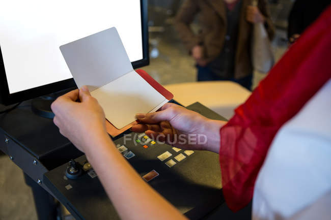 Mid section of female staff checking boarding pass in counter at airport terminal — Stock Photo