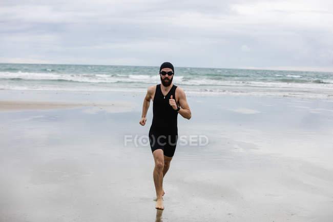 6749718b07e Man in swimming costume and swimming cap running on beach — Stock Photo