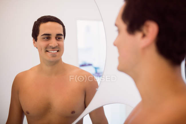 Man smiling while standing in front of mirror in clinic — Stock Photo