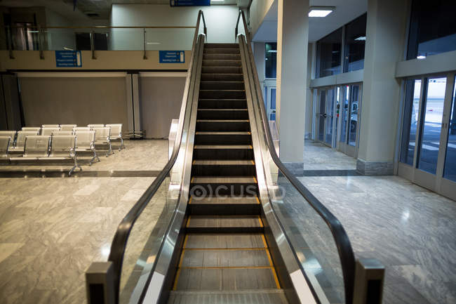 Empty escalator next to waiting area in airport terminal — Stock Photo