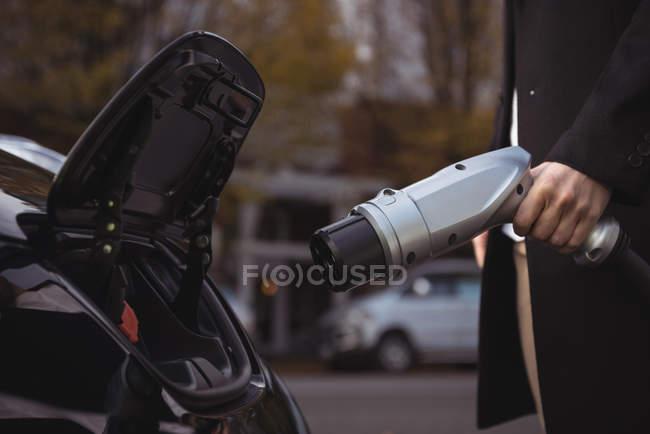 Partie médiane de l'homme chargeant la voiture électrique à la station de recharge du véhicule électrique — Photo de stock
