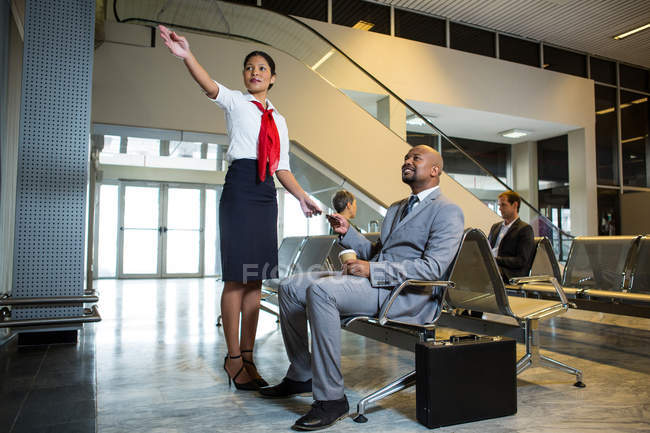 Funcionários do sexo femininos, mostrando a direção ao empresário no aeroporto terminal — Fotografia de Stock