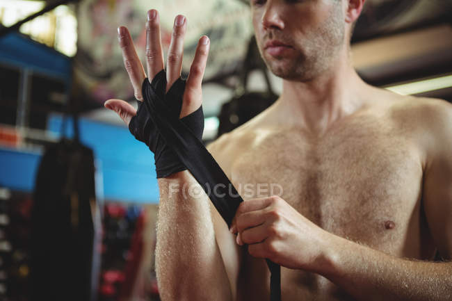 Mid section of boxer wearing black strap on wrist in fitness studio — Stock Photo