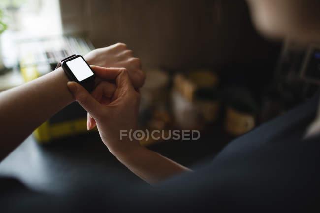 Mid-section de mulher usando relógio inteligente em casa — Fotografia de Stock
