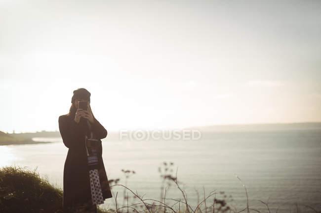 Femme prenant des photos sur téléphone portable par une journée ensoleillée — Photo de stock