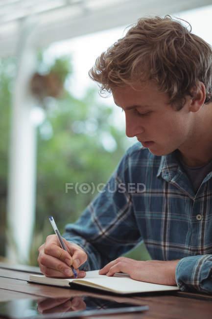 Людина сидить в бюро, писати щоденник вдома — стокове фото