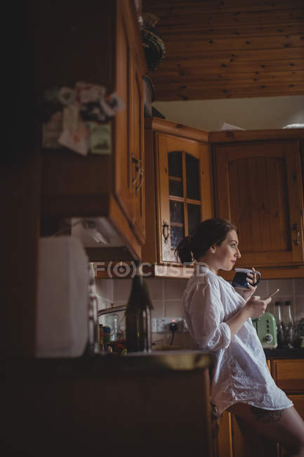 Beautiful woman using mobile phone while having coffee in kitchen at home — Stock Photo