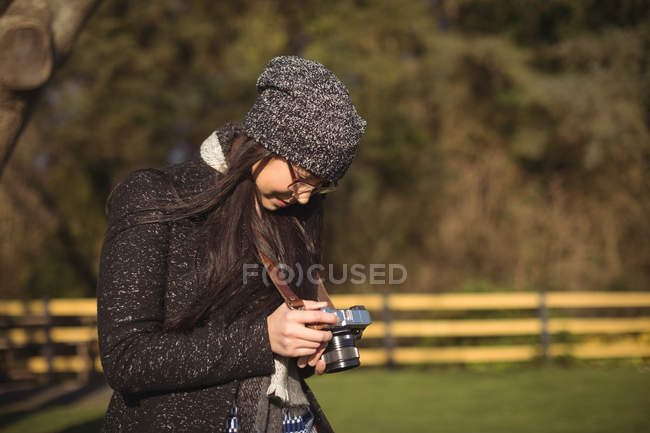 Rear view of woman looking at photos on digital camera on a sunny day — Stock Photo