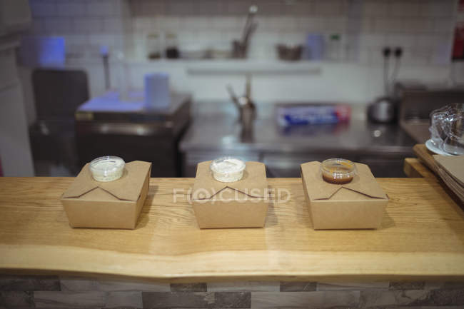 Three boxes of packed meals and sauces on wooden table at restaurant counter — Stock Photo