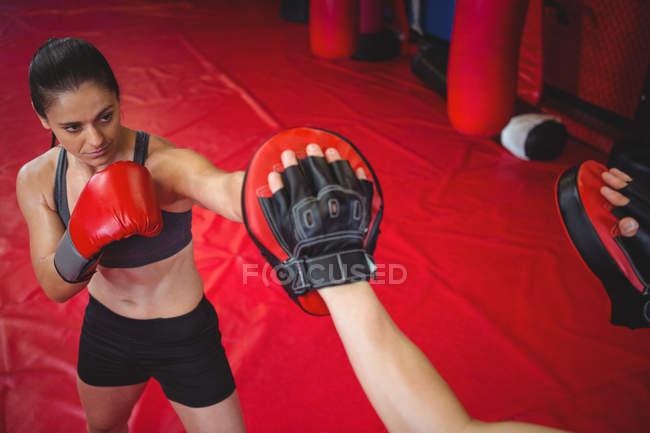 Boxeuse pratiquant avec l'entraîneur à la salle de fitness — Photo de stock