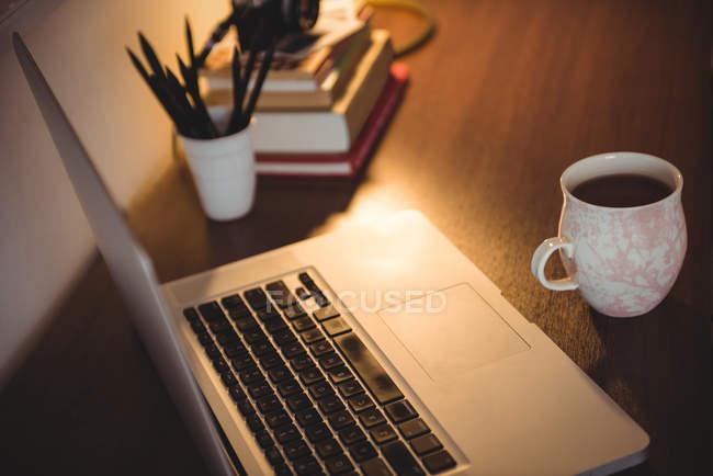 Laptop und Tasse Kaffee auf Holztisch im heimischen Wohnzimmer — Stockfoto