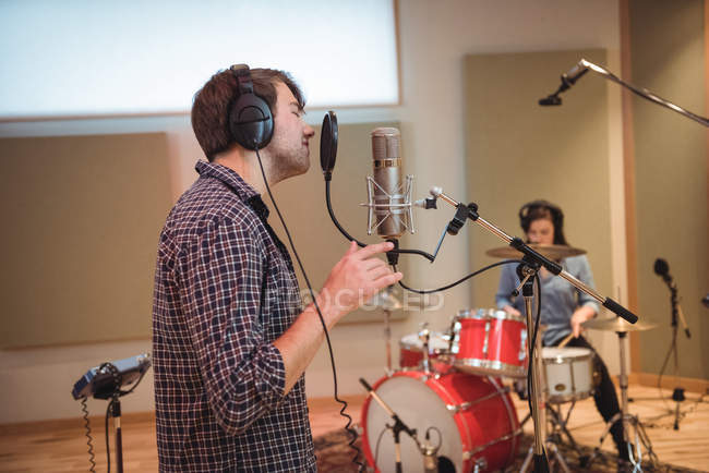 Man singing on microphone in recording studio — Stock Photo