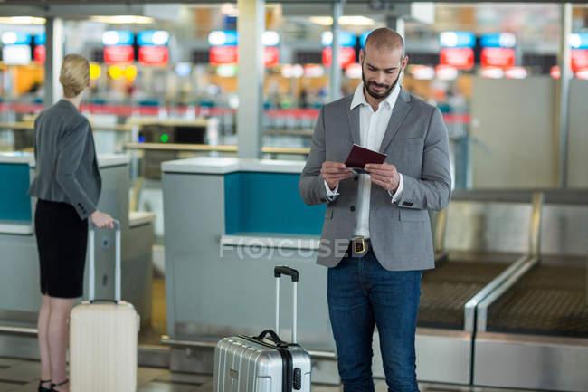Homme d'affaires avec bagages enregistrant sa carte d'embarquement au terminal de l'aéroport — Photo de stock