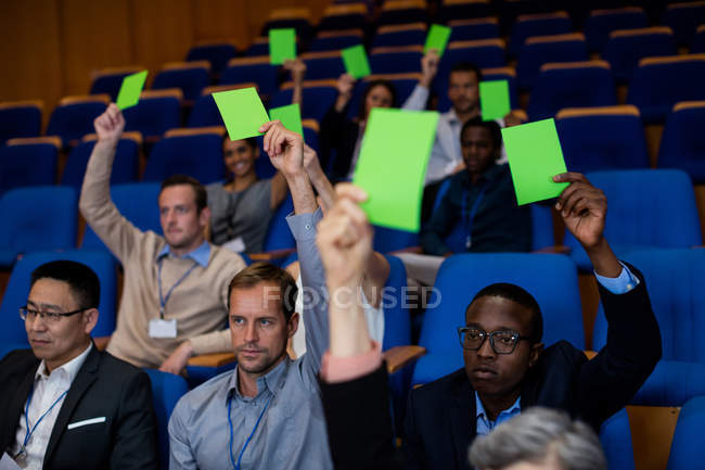 Business executives show their approval by raising hands at conference center — Stock Photo