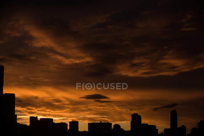 Vista tranquila de las siluetas del paisaje urbano durante la puesta del sol - foto de stock
