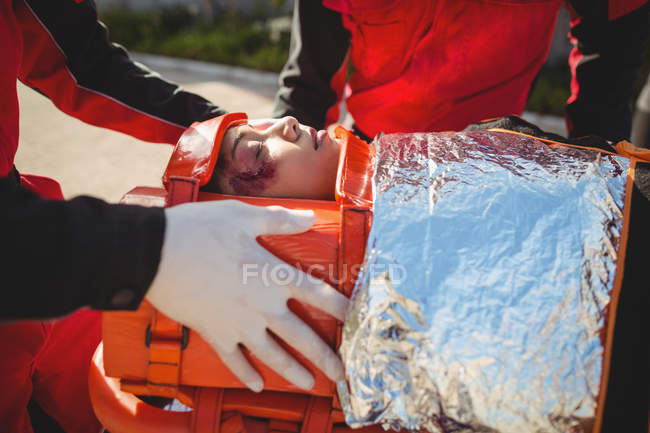 Injured woman treated by paramedic at accident spot — Stock Photo