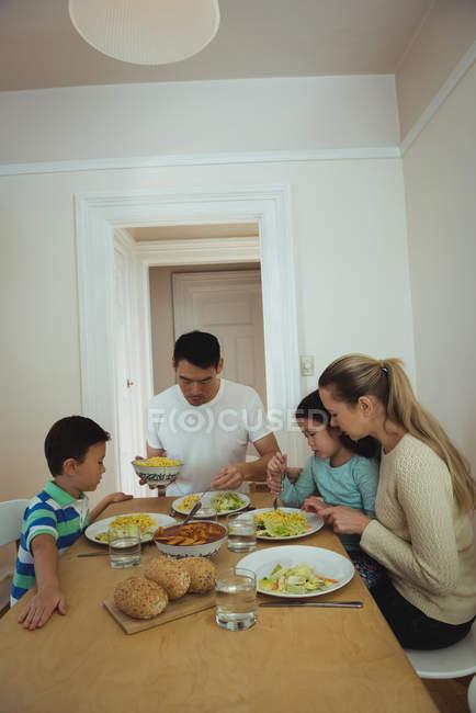 Famiglia che mangia sul tavolo da pranzo a casa — Foto stock