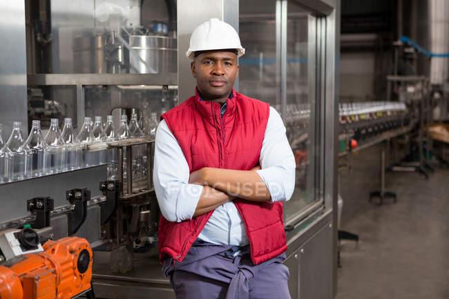 Портрет уверенного работника мужского пола, стоящего у производственной линии на соковом заводе — стоковое фото