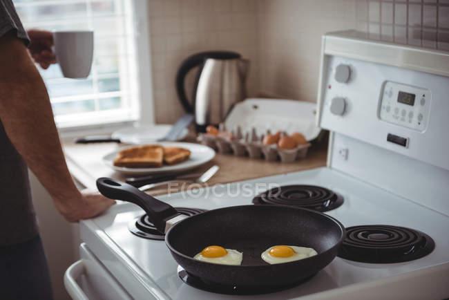 Ovos fritos em uma frigideira na cozinha em casa — Fotografia de Stock